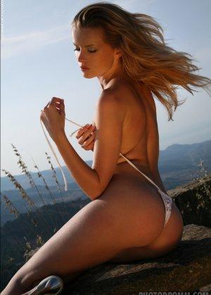 Красивая телочка обнажила свое изысканное тело на природе у скалы - фото 5