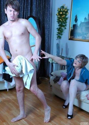 Зрелая бабка пристает к молодому мужу хозяйки, она снимает с него трусы и сосет его хер - фото 18