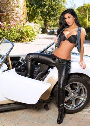 Опытная модель показывает свои нежные сиськи стоя возле машины - фото 1