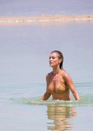 Девушка с натуральными сиськами и мокрым купальником улыбается на телефон - фото 3