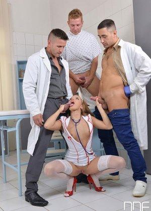 Красивая рыжая медсестра с наслаждением сосет хуи сразу трем своим пациентам в своем рабочем кабинете - фото 6