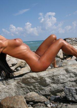 Сексуальная модель со стажем снимает свой влажный купальник на пляже - фото 3