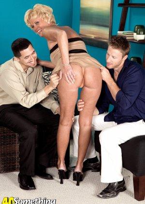 Зрелая белокурая проститутка занимается еблей в два ствола сразу - фото 7