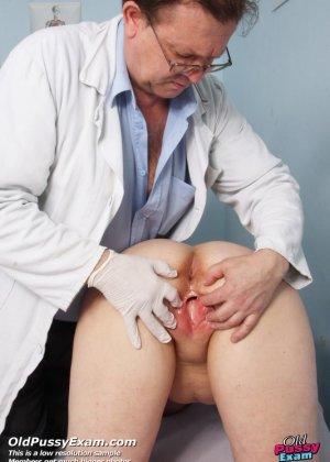 Женщина в зрелом возрасте показывает себя со всех сторон опытному врачу, раздвигая перед ним ноги - фото 4