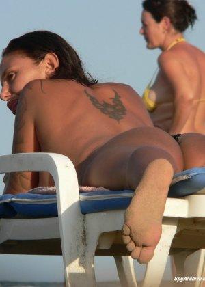 Горячая пышная дамочка в татуировках загорает на пляже и совсем не стесняется обнажаться - фото 4