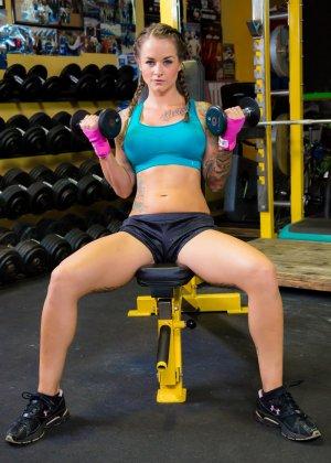 Девушка занимается фитнесом, а затем показывает свое красивое тело с большими татуировками - фото 1