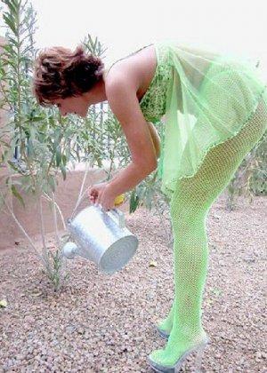 Зрелая кукла показывает свои достоинства когда поливает цветы в саду - фото 5
