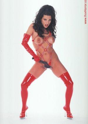 Роковая брюнетка в красном латексе позирует перед фотографом, обнажая самые соблазнительные части тела - фото 3