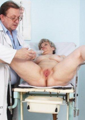 Женщина в зрелом возрасте показывает себя со всех сторон опытному врачу, раздвигая перед ним ноги - фото 10