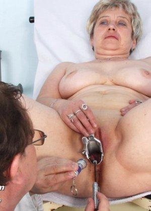 Женщина в зрелом возрасте показывает себя со всех сторон опытному врачу, раздвигая перед ним ноги - фото 14