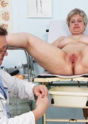 Женщина в зрелом возрасте показывает себя со всех сторон опытному врачу, раздвигая перед ним ноги - фото 13