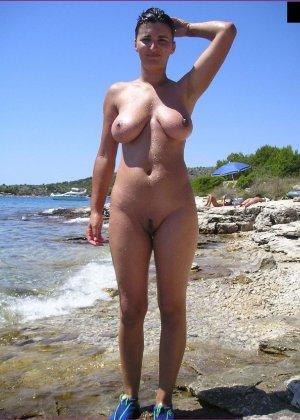 Грудастая зрелая телочка отдыхает на море в голом виде - фото 1