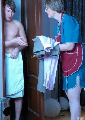 Зрелая бабка пристает к молодому мужу хозяйки, она снимает с него трусы и сосет его хер - фото 3