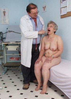 Женщина в зрелом возрасте показывает себя со всех сторон опытному врачу, раздвигая перед ним ноги - фото 7