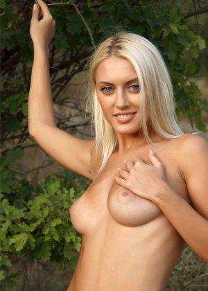 Блондинка на природе позирует перед фотоапаратом в сексуальных позах - фото 48
