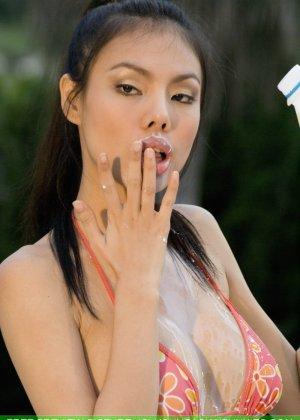 Молодая азиатка сексуально пьет молоко перед камерой и обливает сиськи - фото 6