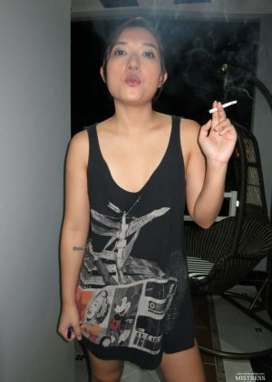 Молоденькая азиатская девушка со стройными ножками нервно курит - фото 5