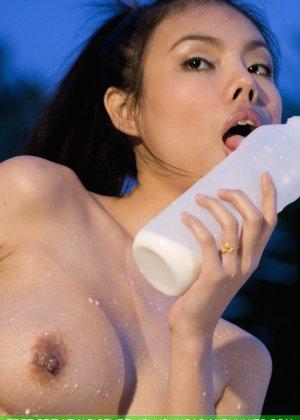 Молодая азиатка сексуально пьет молоко перед камерой и обливает сиськи - фото 16