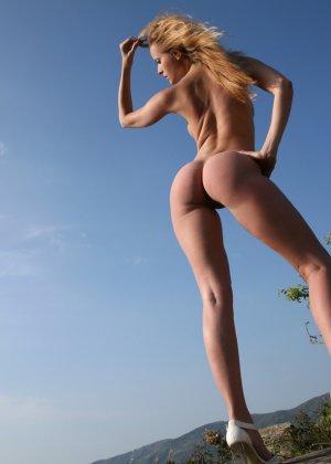 Красивая телочка обнажила свое изысканное тело на природе у скалы - фото 9