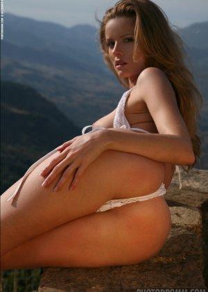 Красивая телочка обнажила свое изысканное тело на природе у скалы - фото 3