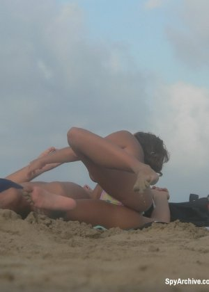 Пока загорающая парочка увлекается друг другом кто-то снимает обнаженную девушку - фото 1