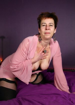 Зрелая женщина в эротичном костюме показывает себя всю, принимая самые откровенные позы - фото 7