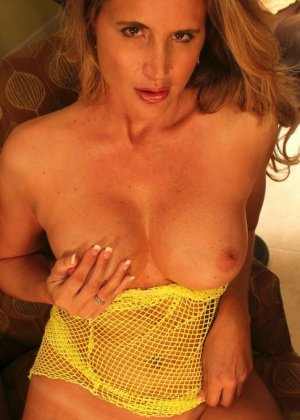 Опытная дамочка показывает свое сексуальное тело, медленно снимая желтую сетчатую маечку - фото 11