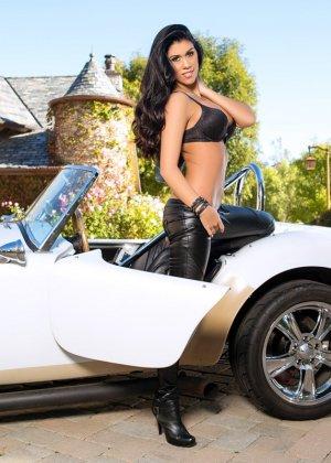 Опытная модель показывает свои нежные сиськи стоя возле машины - фото 5