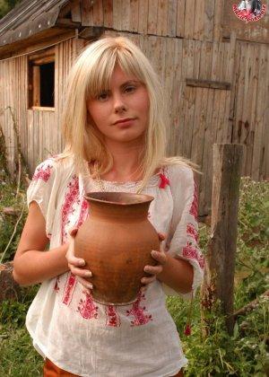 Худенькая блондинка оказывается на сеновале и поливает свое обнаженное тело молоком из кувшина - фото 1