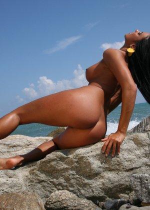 Сексуальная модель со стажем снимает свой влажный купальник на пляже - фото 6