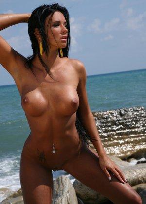 Сексуальная модель со стажем снимает свой влажный купальник на пляже - фото 8