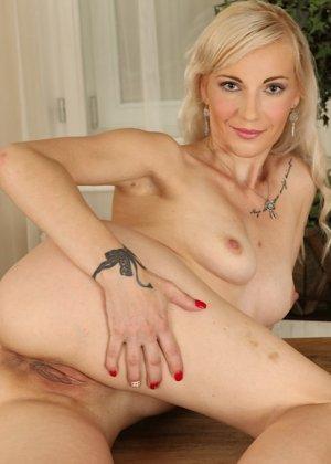 Немолодая блондинка лежит на столе и пальчиками трогает вагинальную дырочку - фото 15