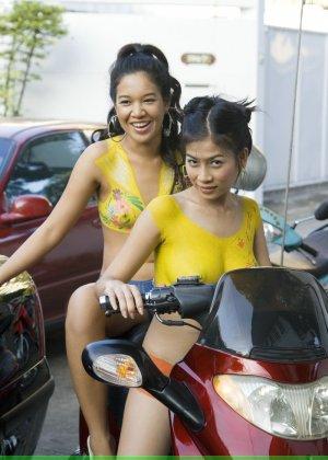 Молодые девушки обливают себя водой в майке без лифчика у мопеда - фото 1