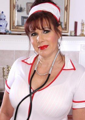 Пышнотелая медсестра сначала позирует в гостиной, а потом теребит свой клитор, получая оргазм - фото 15