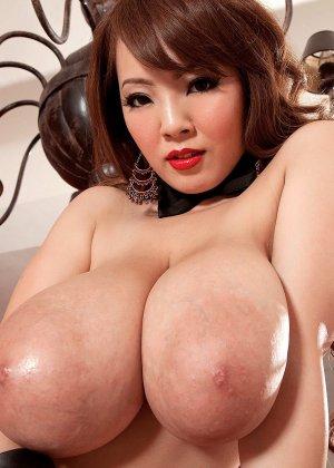 Азиатка с огромными сиськами позирует на камеру вывалив их на стол - фото 5