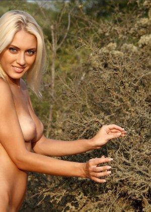 Блондинка на природе позирует перед фотоапаратом в сексуальных позах - фото 15