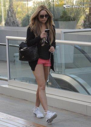 Красивая молодая девушка в наушниках с длинными гладенькими ножками - фото 6