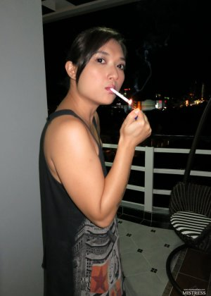 Молоденькая азиатская девушка со стройными ножками нервно курит - фото 11