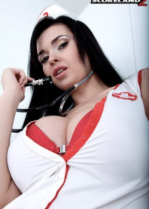 Черноволосая медсестра устроила красивый стриптиз и показала свои большие сиськи - фото 4