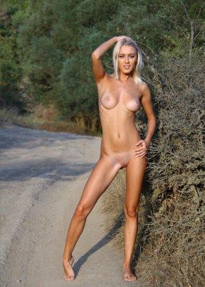 Блондинка на природе позирует перед фотоапаратом в сексуальных позах - фото 19