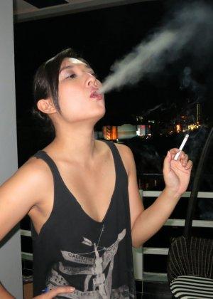Молоденькая азиатская девушка со стройными ножками нервно курит - фото 6