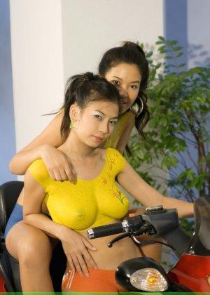 Молодые девушки обливают себя водой в майке без лифчика у мопеда - фото 6