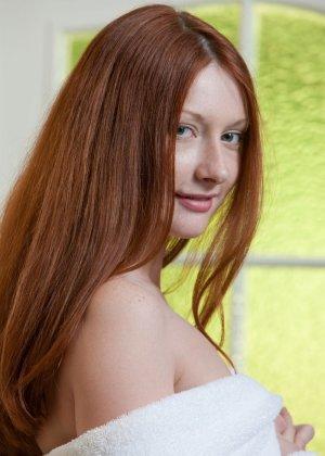 Рыжеволосая девушка принимает разные позы, чтобы показать себя с самых выгодных ракурсов - фото 1