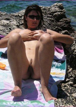 Грудастая зрелая телочка отдыхает на море в голом виде - фото 2