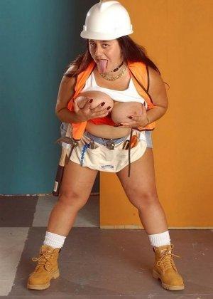 Толстая женщина в белой каске сидит на стуле и облизывает сиськи - фото 2