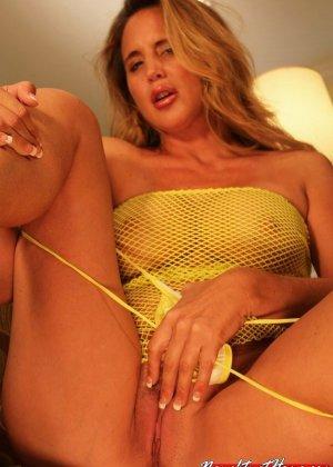 Опытная дамочка показывает свое сексуальное тело, медленно снимая желтую сетчатую маечку - фото 10