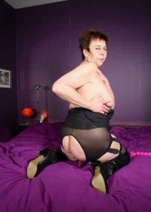 Зрелая женщина в эротичном костюме показывает себя всю, принимая самые откровенные позы - фото 16