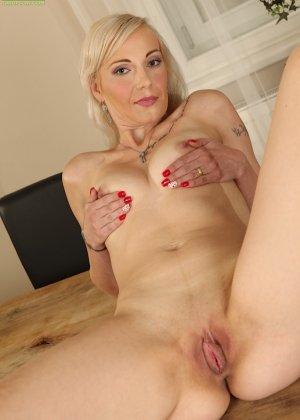 Немолодая блондинка лежит на столе и пальчиками трогает вагинальную дырочку - фото 13