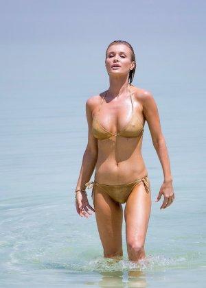 Девушка с натуральными сиськами и мокрым купальником улыбается на телефон - фото 6