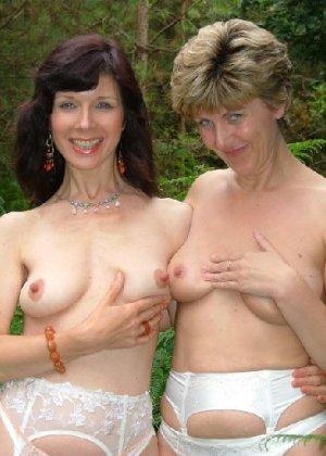 Две зрелых лесбиянки сосутся на природе и ласкают свои дырочки - фото 28